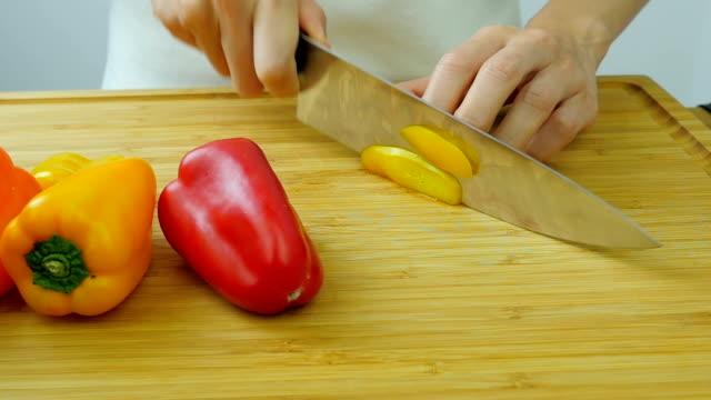 Cutting bell pepper on wooden table. video