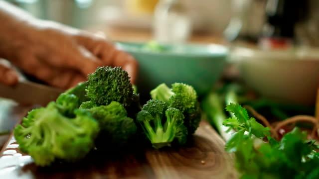cetriolo che viene broccoli su un tagliere per nasi goreng - broccolo video stock e b–roll