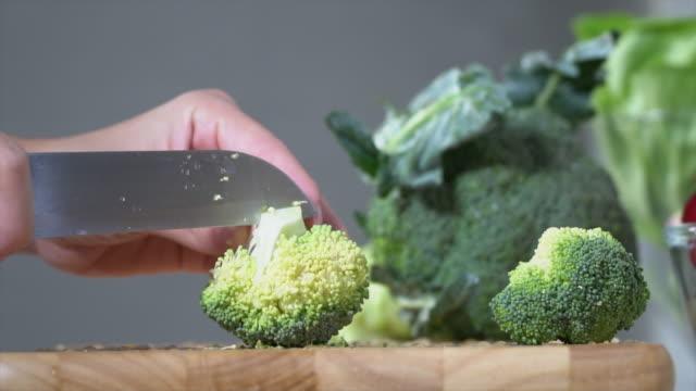vídeos y material grabado en eventos de stock de cortar brócoli en una tabla de cortar - pak choy