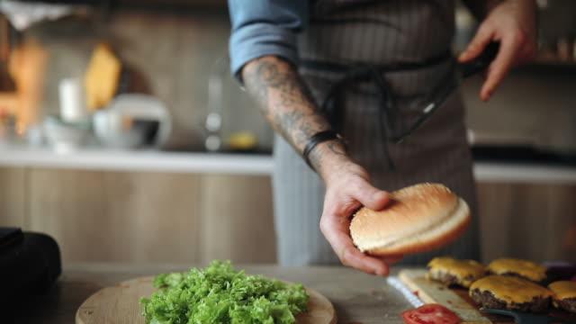 cutting bun for delicious cheeseburgers - cheeseburger filmów i materiałów b-roll