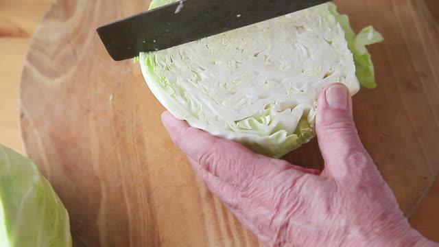 cutting cabbage into quarters - crucifere brassicali video stock e b–roll