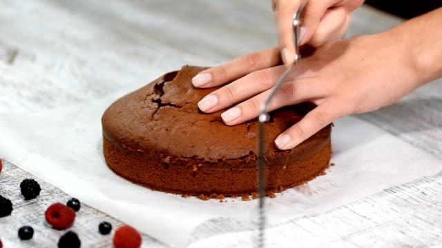 katmanlar üzerinde kek kesme. çikolata tabakası pasta yapma. - kek dilimi stok videoları ve detay görüntü çekimi