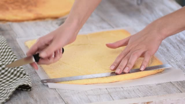 Cutting Cake on Layers. Woman is trimming the edges of the cakes