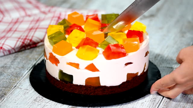 Cutting cake with colorful fruity jelly pieces. Cutting cake with colorful fruity jelly pieces. jello stock videos & royalty-free footage