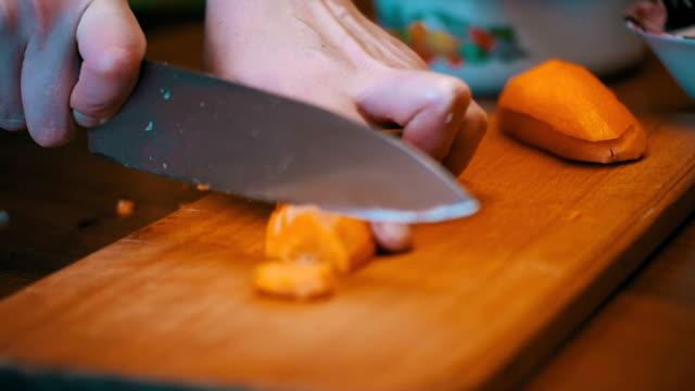 家庭の台所でまな板でスライスにニンジンをカット。スローモーション - ローフード点の映像素材/bロール