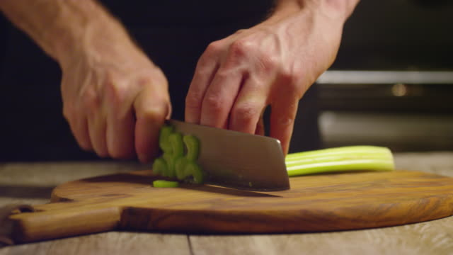 Cutting Celery on a Wooden Chopping board for Christmas A chef cutting celery on a round wooden chopping board for his Christmas recipe. celery stock videos & royalty-free footage