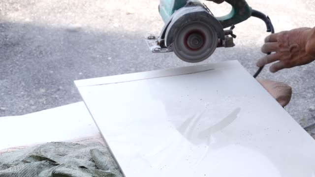 cutting ceramic tile with hand mill - piastrella video stock e b–roll