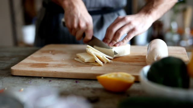 Cutting cheese CLose up of man cutting with a kitchen knife cheese or butter on chopping board. cheese stock videos & royalty-free footage