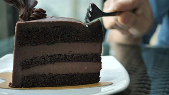 Cutting Chocolate cake in the cafe