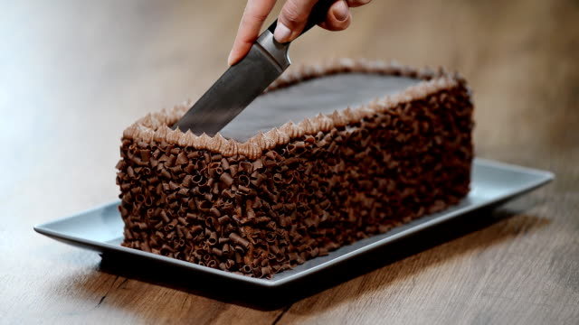 Cutting chocolate cake on table,close up video