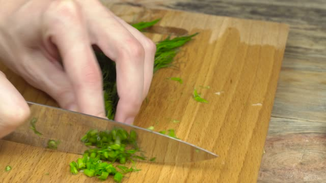 cutting fresh green onions on a cutting board. - alliacee video stock e b–roll