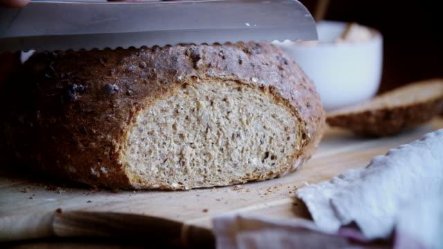 vídeos de stock e filmes b-roll de cutting fresh homemade brown bread - baking bread at home