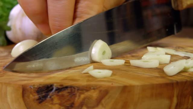 Cutting garlic on a wooden cutting board - video