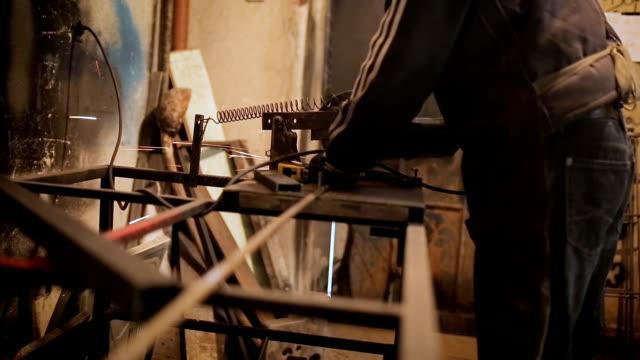 stockvideo's en b-roll-footage met snijden ijzer in smid winkel - metaalbewerking