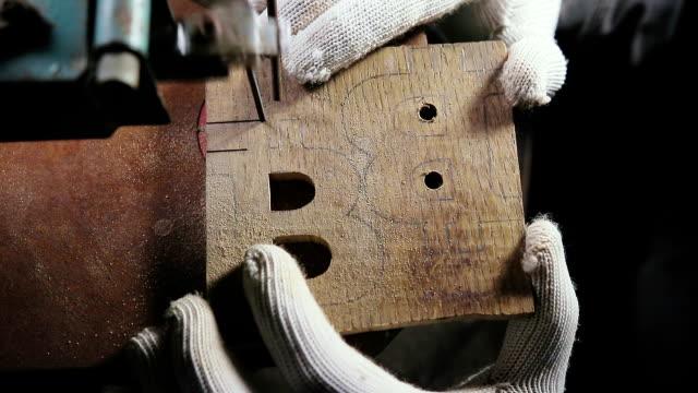 vídeos de stock e filmes b-roll de cutting jigsaw in a wooden workpiece, the symbol of bitcoin - circular economy