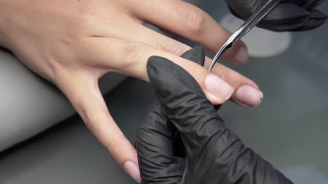 vidéos et rushes de couper les cuticules des ongles de ciseaux à ongles dans salon de manucure professionnel. manucure et beauté des ongles féminins. - cuticule