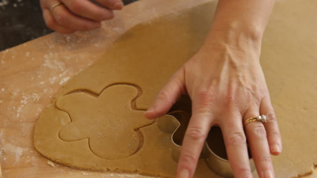 Cutting out gingerbread men cookies Cutting out gingerbread men cookies cookie cutter stock videos & royalty-free footage
