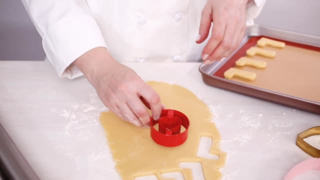 Cutting out shapes from sugar cookie dough with cookie cutters. Step by step. Cutting out shapes from sugar cookie dough with cookie cutters. cookie cutter stock videos & royalty-free footage