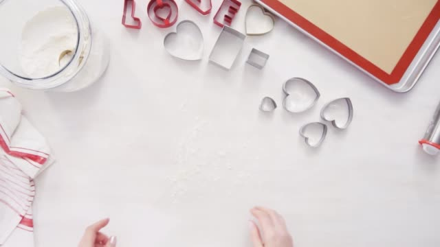 Cutting out shapes from sugar cookie dough with cookie cutters. Flat lay. Step by step. Cutting out shapes from sugar cookie dough with cookie cutters. cookie cutter stock videos & royalty-free footage