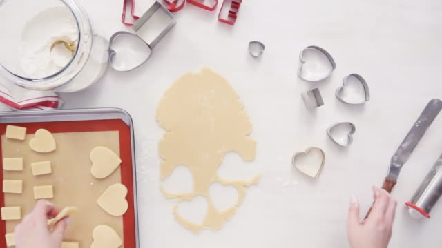 Video Cutting out shapes from sugar cookie dough with cookie cutters.