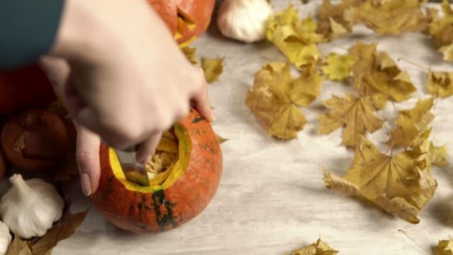 cutting out the inside of a pumpkin for a halloween lantern decoration - zucca legenaria video stock e b–roll