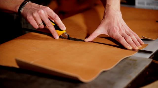styckningen av en handgjord produktionstillbehör från läder, händer av man - läder bildbanksvideor och videomaterial från bakom kulisserna