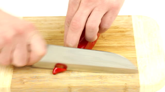 cutting red chili pepper cutting red chili pepper, Video of preparing food filmed in full HD with white background paprika stock videos & royalty-free footage