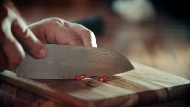 Cutting Red Chilies with Knife on Kitchen Board video
