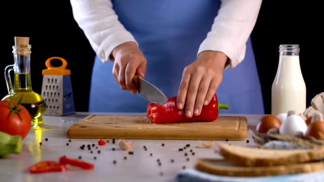 vídeos de stock e filmes b-roll de cutting red pepper on chopping board - red bell pepper isolated