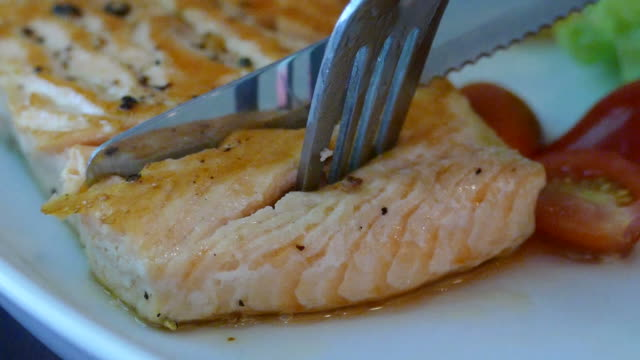 cutting salmon steak - slowmotion video