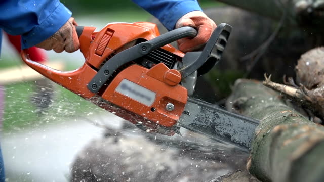 Cutting through wood with chainsaw in slow motion video