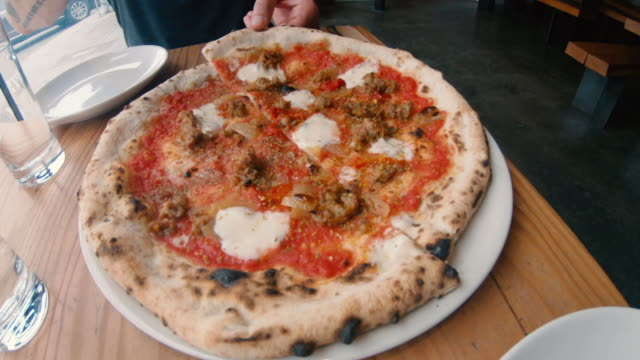 cutting wood fired goat cheese chorizo sausage onions thin crust pizza with scissors fancy italian restaurant - forbici video stock e b–roll