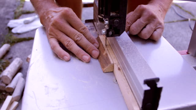 Cutting wood plank using bandsaw, close-up video