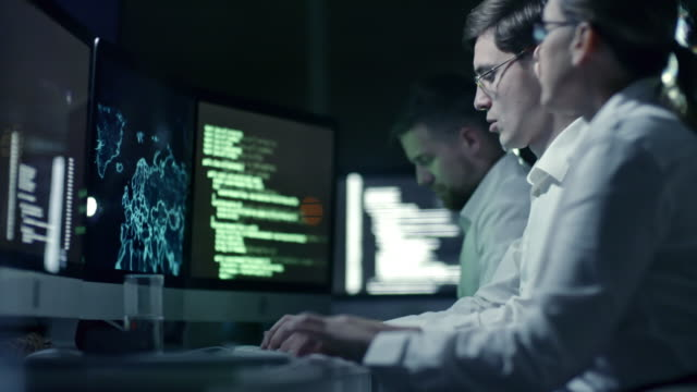 Cyber Security Team Working Night-Shift Professional team of cyber security specialists writing program code and working with holographic map on computers in IT office at night encryption stock videos & royalty-free footage