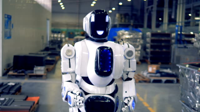 A cyborg goes forward in a factory floor. Close up. A white droid walks forward, looking at the sides. cyborg stock videos & royalty-free footage