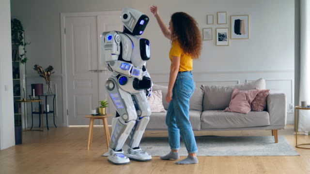 vídeos de stock e filmes b-roll de a cyborg is dancing after getting hugged by a lady - future hug