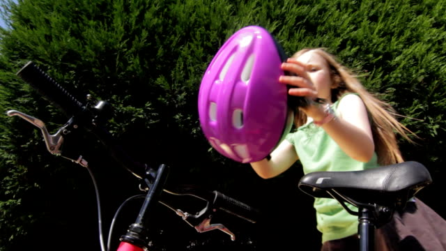 Cycle helmet A little girl puts on her cycle helmet and rides off. work helmet stock videos & royalty-free footage