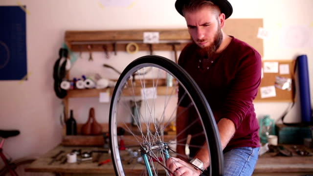 Cycle mechanic repairs the wheel of a bicycle. video