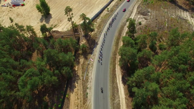 Cycling race on country road. Drone view group cyclists racing highway