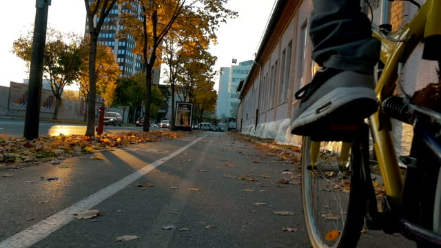 Cycling trugh a city in a beautiful autumn sunset video