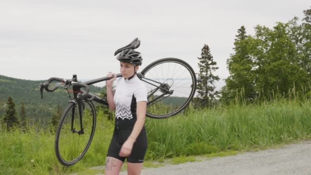 A cyclist carries her bike to the starting point.