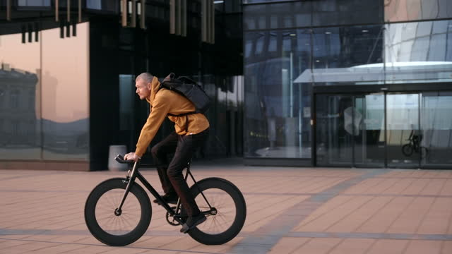 A cyclist in a red jacket rides through the city past modern glass buildings A cyclist in a red jacket rides through the city past modern glass buildings treedeo speed way stock videos & royalty-free footage