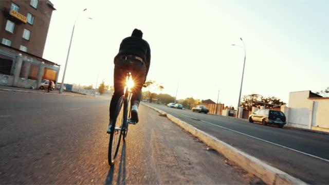 乗って自転車男は、晴れた日にギアのスポーツ バイクを固定都市の夕暮れ - サイクリング点の映像素材/bロール