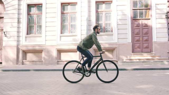 Cyclist man riding fixed gear sport bike in sunny day on a city video