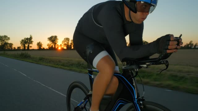a cyclist peddles hard along a country road at sunset/sunrise. - evento ciclistico video stock e b–roll