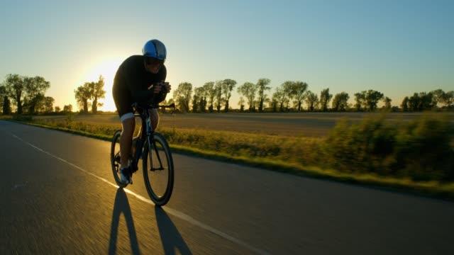 Ein Radfahrer hausieren hart entlang einer Straße bei Sonnenaufgang/Sonnenuntergang. – Video