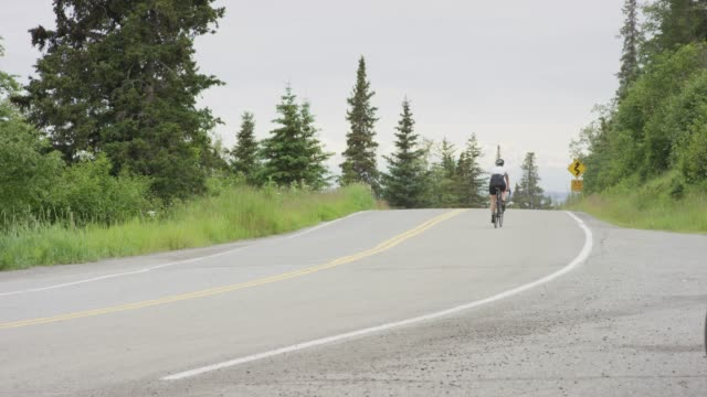 Cyclist rides along a rural highway