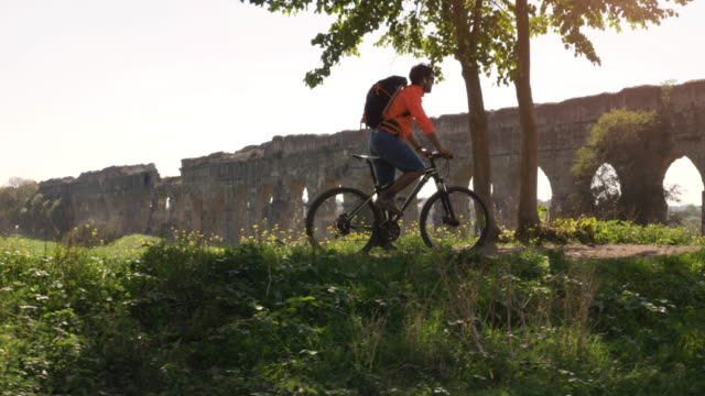 cyclist riding bike in front of ancient roman aqueduct in a park. young attractive athletic man with orange sportswear and backpack in parco degli acquedotti in rome - dolly shot video stock e b–roll