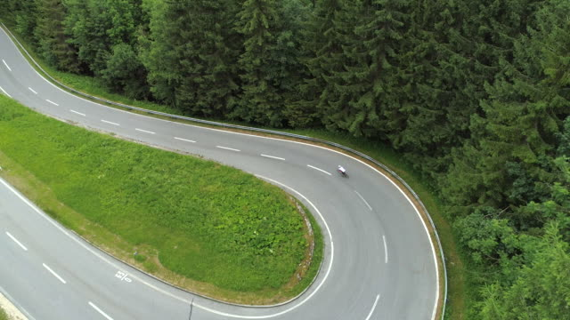 AERIAL: Cyclist riding bike uphill through sharp hairpin bend on mountain road video
