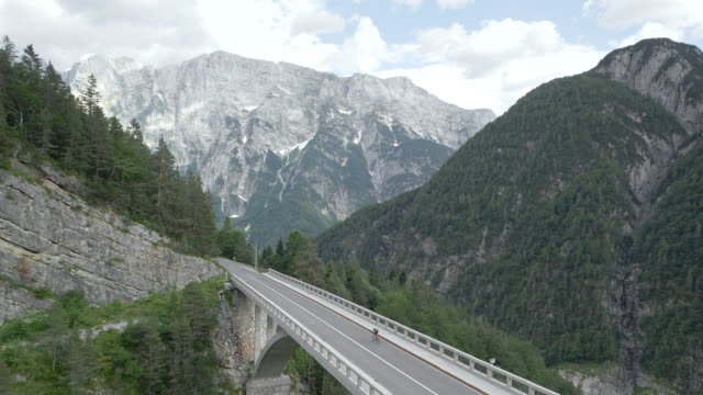 aerial cyclist riding his road bicycle on a nice bridge in the mountains - parapetto barriera video stock e b–roll